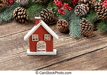 photo of house shaped toy near christmas decorations on the wonderful brown wooden background