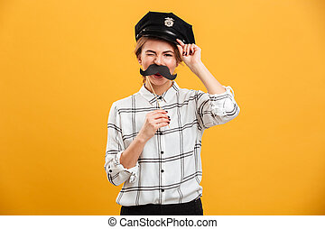 Photo of humorous woman in plaid shirt and police cap holding paper moustache at her face, isolated over yellow background