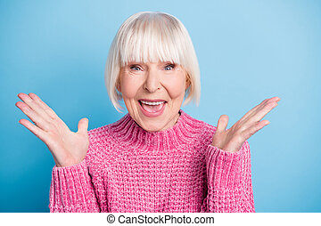 Photo of impressed cheerful person hands palms up open mouth smile wear pullover isolated on blue color background