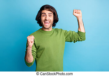 Photo of impressed person two fist up open mouth yeah celebrate green pullover isolated on blue color background