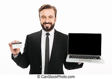 Photo of joyful businessman in suit smiling and showing laptop and plastic credit card on camera, isolated over white background
