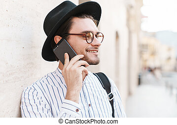 Photo of joyful caucasian man talking on cellphone and smiling while leaning on wall in city street