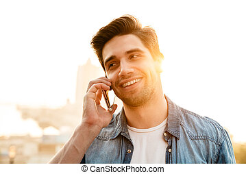 Photo of joyful handsome man smiling and talking on mobile phone