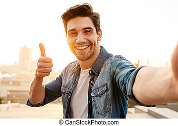 Photo of joyful young man showing thumb up while taking selfie