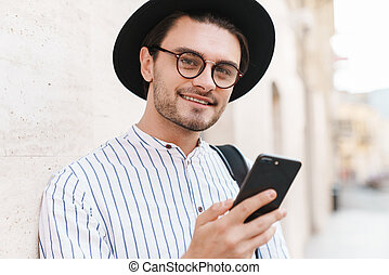 Photo of joyful young man typing on cellphone and smiling while leaning on wall in city street