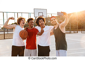 Photo of joyous sporty guys smiling and taking selfie on smartphone while playing basketball at playground outdoor during summer sunny day