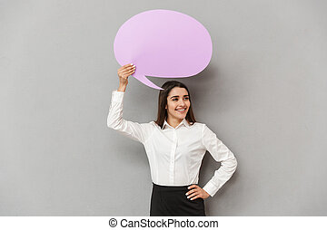 Photo of joyous woman in white shirt and black skirt looking aside with smile while holding copyspace bubble for text, isolated over gray background