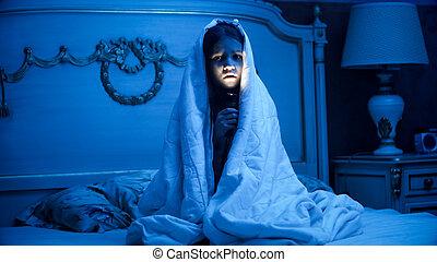 Photo of little girl covering under blanket holding flashlight in dark room