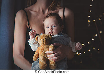 Photo of little infant in mother's hands with teddy bear toy