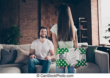 Photo of little lady holding behind back prepared birthday big green giftbox for handsome daddy sitting cozy sofa affectionate smiling blurry focus house room indoors