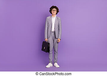 Photo of little schoolkid guy hold case stand posing wear spectacles grey suit isolated purple color background