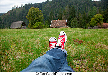 photo of male legs in jeans and red gumshoes on the wonderful village background