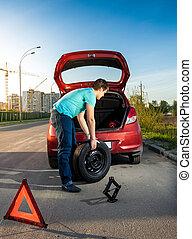 man changing punctured wheel on broken car