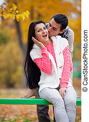 photo of man kissing his woman on the wonderful autumn trees background