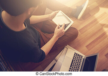 Photo of man touching screen Of generic design tablet holding in his hands. Laptop on the floor.