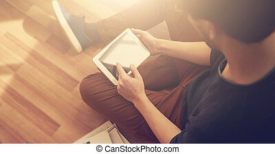 Photo of man touching screen Of generic design tablet holding in his hands.