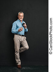 Photo of mature man 60s with grey hair and beard using ell...