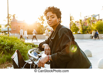 Photo of modern african american woman looking at camera while sitting on bicycle in city park