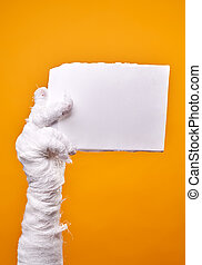 Photo of mummy's hand and blank paper on empty orange background .