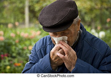 photo of old man blowing his nose
