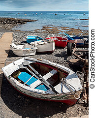 Photo of old painted wooden rowing boats lying on the sea beach next to the pier