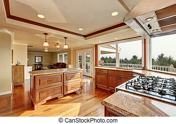 Photo of open concept kitchen with cabinets and granite...