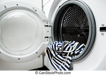 Photo of open washing machine with striped cloth, close-up