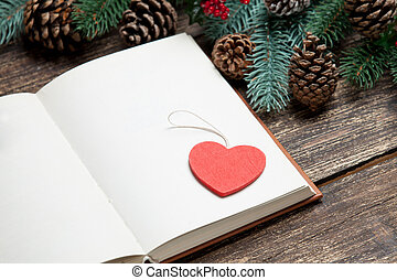 photo of opened notebook and heart shaped toy near christmas decorations on the wonderful brown wooden background