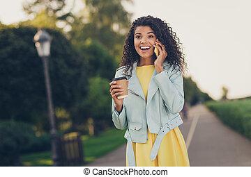 Photo of optimistic cool brunette hairdo lady drink tea talk telephone wear yellow dress jacket outside in park