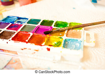 Photo of palette with watercolors and brush