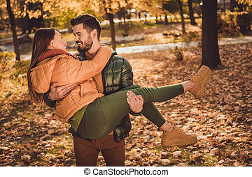 Photo of passionate bonding couple man hold hug his girlfriend in fall october forest park wear season coats