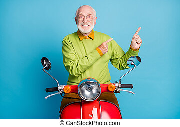Photo of pensioner grandpa drive scooter direct finger empty space wear spectacles green pullover isolated blue color background