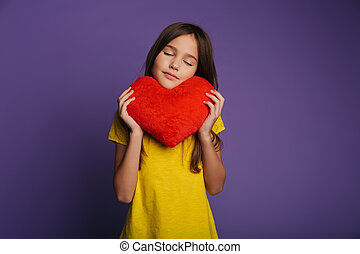 Photo of pleased girl holding soft toy heart with eyes closed