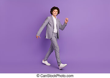 Photo of positive carefree pupil guy walk school break wear grey suit isolated violet color background