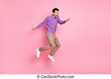 Photo of positive cute young guy wear violet sweater jumping high looking empty space isolated pink color background