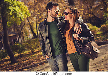 Photo of positive hipsters guy embrace his girlfriend in yellow october forest town park wear rucksack