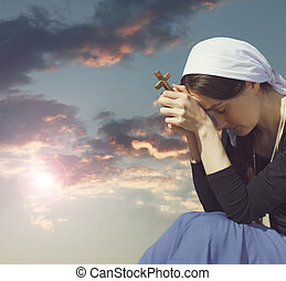 Photo of young woman praying during sunset