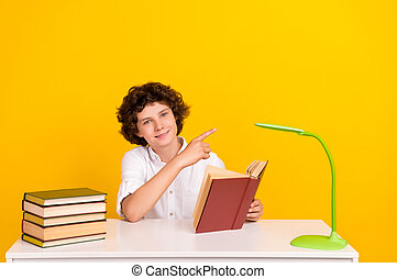 Photo of pretty cute school boy wear white shirt smiling reading book pointing empty space isolated yellow color background