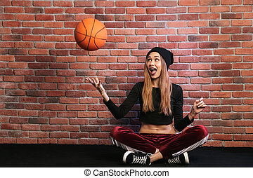 Photo of pretty sporty girl 20s, sitting on floor against brick wall and playing with basketball