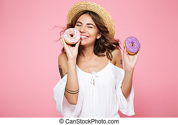 Photo of pretty young brunette woman in straw hat holding sweet donuts with closed eyes