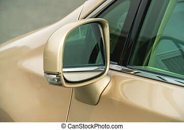 Photo of rear-view side mirror on a gold-coloured car