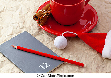 Photo of red cup of coffee, diary with red pencil. Plans for December.