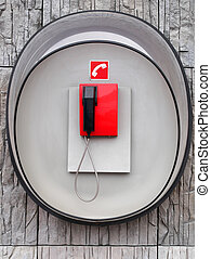 Photo of red phone on gray wall of modern building