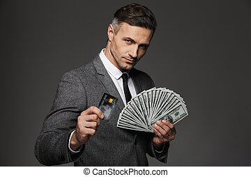 Photo of rich man 30s in business suit holding fan of dollar cash and digital money on credit card, isolated over gray background