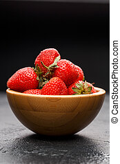 Photo of ripe strawberry in wooden cup on black background