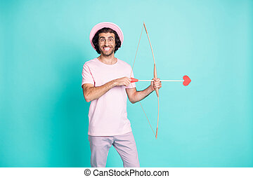 Photo of romantic man hold bow shoot arrow wear pink cap spectacles t-shirt pants isolated on teal color background