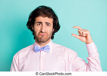 Photo of sad stubble curly brunet hair gentleman dressed pink outfit measure fingers empty space isolated teal color background