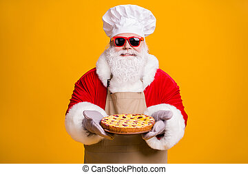 Photo of santa claus chef headwear grandpa grey beard hold ready fresh sweet big pie with jam wear x-mas costume gloves sun specs cap apron isolated yellow color background