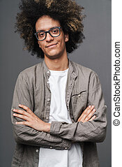Photo of satisfied young man with afro hairstyle poising with arms crossed