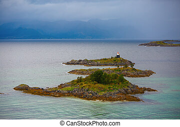 Photo of sea, hills, lighthouse, sky in Norway on summer.